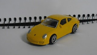 Porsche 911 Carrera , escala 1/64 , color amarillo , de Majorette .